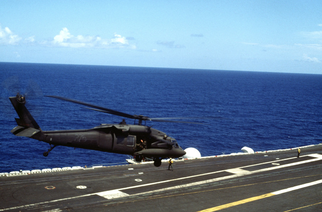A UH-60 Black Hawk (Blackhawk) helicopter is guided in for a landing on deck of the aircraft carrier during an air assault rehearsal