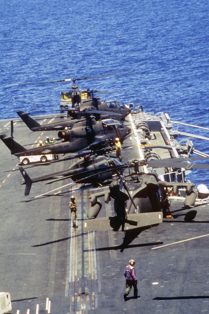 A view looking forward on the starboard side of the flight deck of the nuclear-powered aircraft carrier USS DWIGHT D. EISENHOWER (CVN-69) en route to Haiti. Helicopters from the Army's 10th Mountain Division, Fort Drum, N.Y. are parked on deck during an air assault rehearsal. They include an AH-60 Blackhawk, an OH-58 Kiowa observation helicopter and several AH-1 Cobra attack gunship helicopters