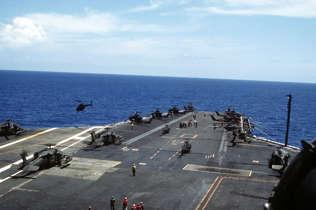 AH-1 Cobra Gunship helicopters standby for take off during an air assault rehearsal on the aircraft carrier. UH-60 Black Hawk (Blackhawk)s are in the foreground