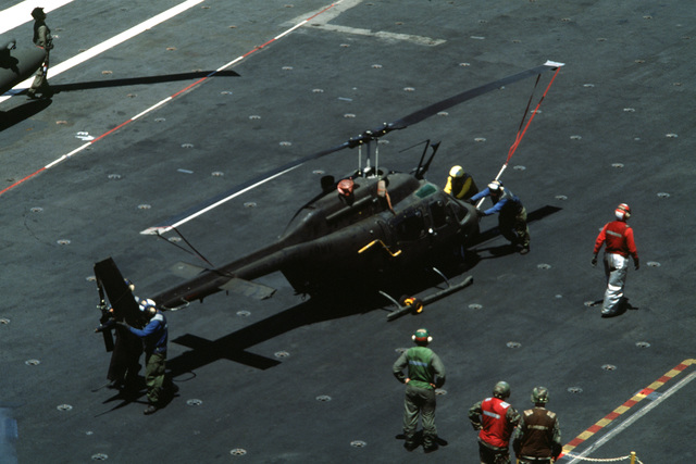 Flight deck crews on board the carrier repositions an OH-58 Kiowa helicopter to prepare for flight operations