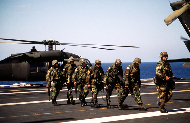 Soldiers from A Company, 2nd Brigade, 22nd Light Infantry Division, cross the flight deck after completing a mock air assault in a UH-60 Black Hawk (Blackhawk) on in preparation for the Haiti invasion