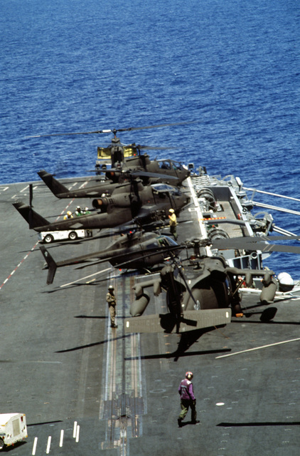 US Army Cobra Gunship helicopters stand by for take off during an air assault rehearsal on board the aircraft carrier