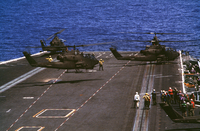 US Army Cobra gunship helicopters standby for take off during an air assault rehearsal on board the aircraft carrier