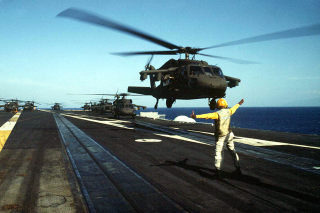 A UH-60 Black Hawk (Blackhawk) helicopter from the 3-25 Assault Helicopter Battalion takes-off from the deck of the aircraft carrier USS Eisenhower (CVN-69) taking the first wave of combat troops ashore in Haiti, 19 Sep 94. More Black Hawk (Blackhawk)s are in line waiting for take-off