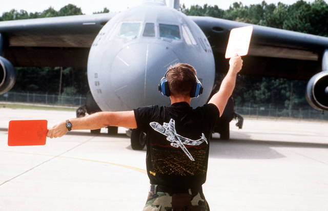 SENIOR AIRMAN Robert Bryner, Jet Engine Maintenance, 62nd Mobility Squadron, McChord AFB, WA, directs a C-141 aircraft out of McGuire AFB, NJ, out onto the runway