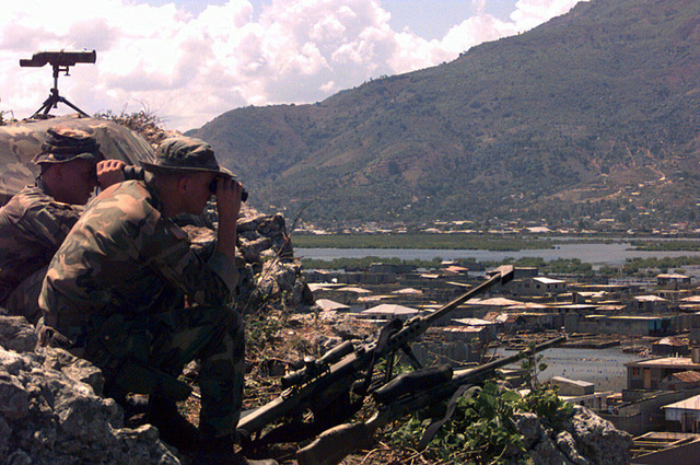 """Corporal Greg Camp (left) and Corporal Joe Cooper of Scout Sniper Platoon 2/2, survey the outskirts of Cap Haitien. Lookouts are posted on """"The Hill"""" 24 hours a day, keeping watchful eyes on the townspeople during Operation Uphold Democracy"""