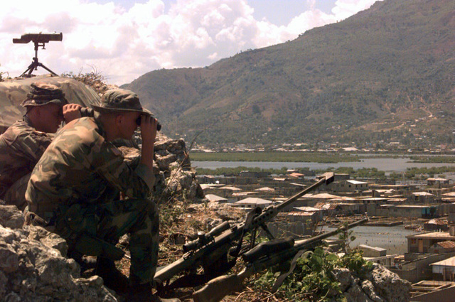 Marine CPL. Greg Camp, far left, and CPL. Joe Cooper of Scout Sniper Platoon 2/2, survey with field glasses, the outskirts of Cap Haitien. In the foreground is a 7.62mm sniper rifle, and next to it is a 50 caliber sniper rifle