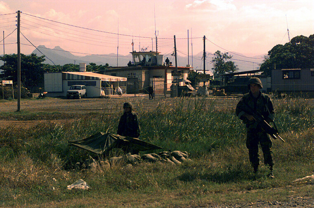 A Marine walks the perimeter of the airfield and another Marine stands at his camouflaged foxhole. They are securing the airfield at Cap Haitien which is used by a special Marine Air-Ground Task Force (MAGTF) during Operation Uphold Democracy