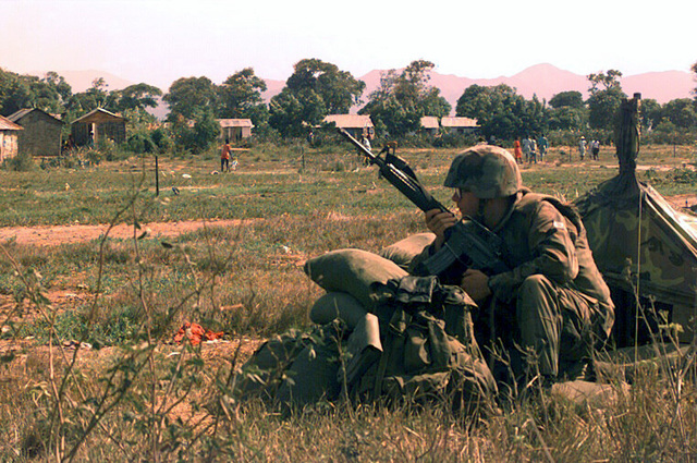 Marine Lance CPL. Jordan holds his M16A2 rifle in the ready position while seated behind sandbags in a grassy field and looking toward civilians and houses. He is providing security for the airstrip during Operation Uphold Democracy