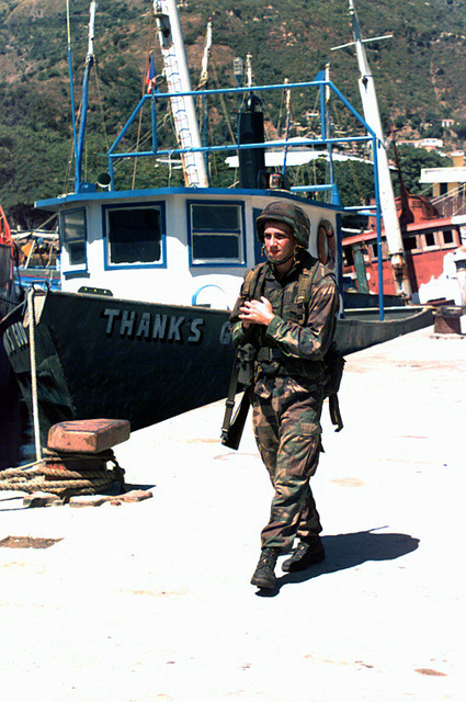 Marine LCpl E. Lampe of H&S Company walks security at the port of Cap Haitien wearing an M-85 Kevlar-lined helmet, flack vest and M-16A2 rifle. The port is a major logistical and command center for the special Marine Air Ground Task Force (MAGTF) for Operation Uphold Democracy