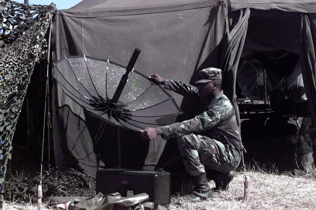 A1C Antonio Byrd, wideband/satcom maintenance for the 3rd CCG Tinker Air Force Base, repositions a TCS-Ultralite satellite dish for better reception. The INMARSAT transportable communications system is one of the primary means of communication for deployed troops