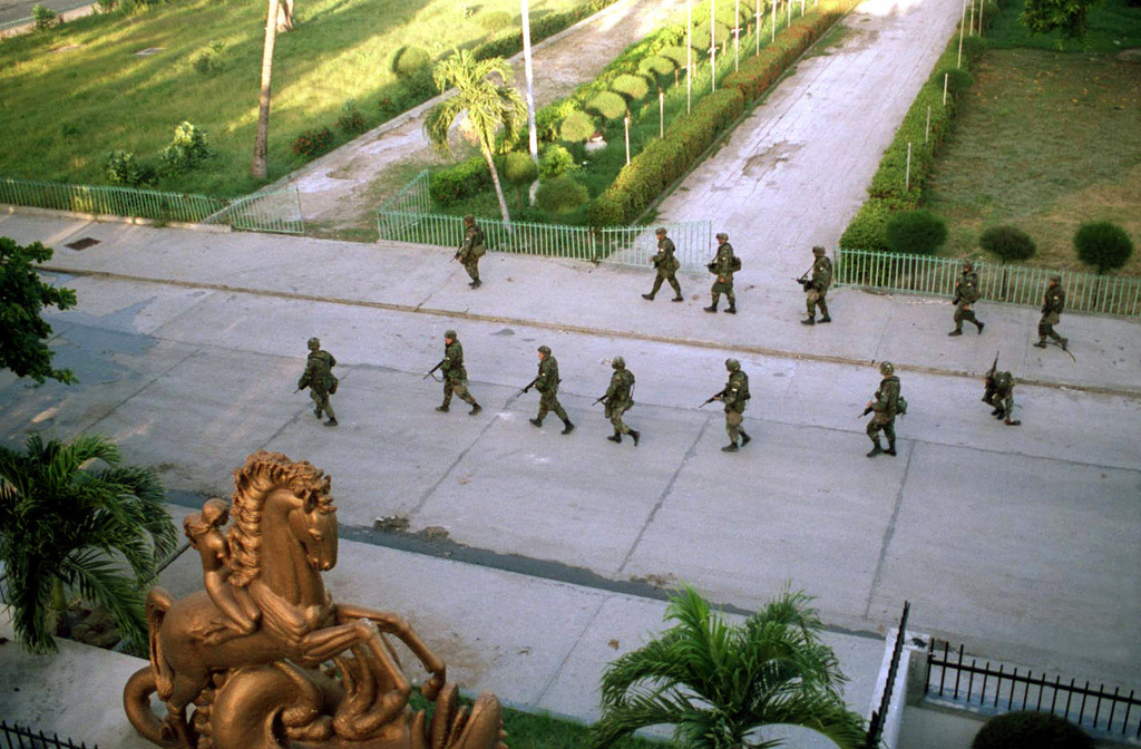 An aerial view of U.S. Army Military Police from the 988th MP Company, 519th MP Brigade, as they fan out with their weapons in front of the Haitian Parliament building on 28 Sep 94. The Parliament is convened to discuss the amnesty issue