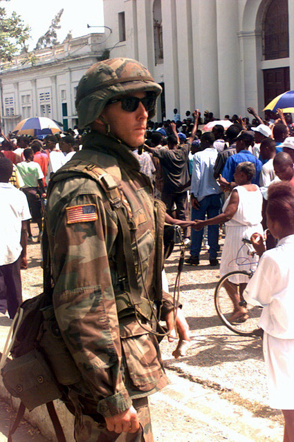 Marine Lance CPL. Langdon of Golf 2/2, stands his position during the Haitian parade. Several civilian Haitian people are standing around a building during Operation Uphold Democracy