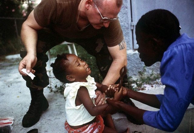 Captain Wille, attached to the 10th Mountain Division, Ft. Drum, NY, treats a young Haitian girl with an infection on her legs as her mother holds her arms. The child lives near the Industrial Complex in Port-au-Prince, Haiti where elements of the 10th Mountain Division are staying during Operation Restore Democracy. Exact Date Shot Unknown