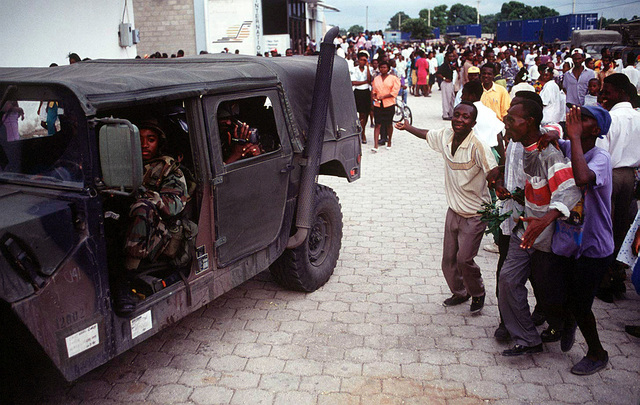 Haitians follow a High-Mobility Multipurpose Wheeled Vehicle (HMMWV) to show their approval of U.S. presence in their country during Operation Uphold Democracy. Exact Date Shot Unknown