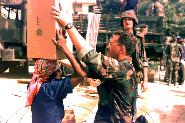 Marine CW02 C. Grow of the Combat Camera Unit helps a Haitian woman balance a box of food on her head. The Marines participated in local relief efforts by transporting and delivering long awaited food to the inner city of Cap Haitien during Operation Uphold Democracy