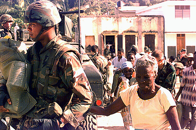 Marine Lance CPL. Long of Headquarters 2/2, carries an elderly civilian Haitian woman's bag of good. Several civilian Haitians behind them are getting their share of food during Operation Uphold Democracy
