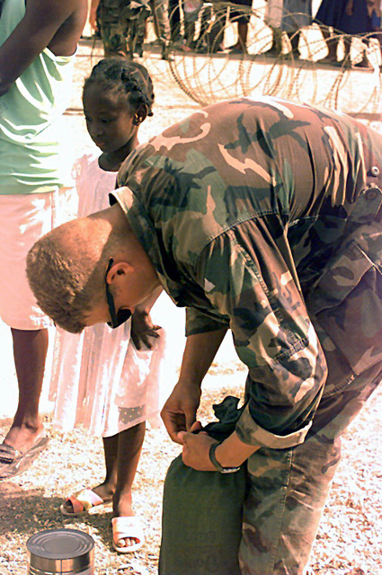 Marine Lance CPL. Sosaman of CSSD 29 is opening a bag with food in it. A young Haitian girl is standing by waiting during Operation Uphold Democracy