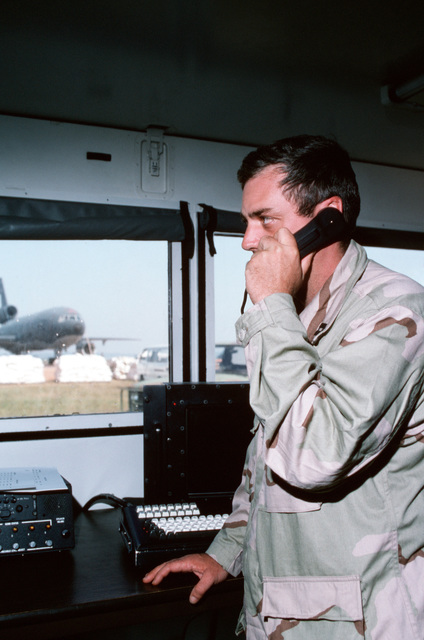 """USAF Captain Ted Lemieux, an operations officer, from McGuire AFB, New Jersey stands and talks on a receiver phone inside the Air Route Traffic Control Center (ARTCC) at Entebbe, Uganda. From AIRMAN Magazine's December 1994 issue article """"Will You Please Pray for US?"""" -Relief for Rwandan Refugees"""