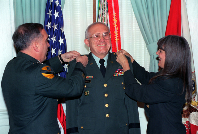 GEN John H. Tilelli, Jr. (left), Army Vice CHIEF of STAFF, pins on major general stars on Robert H. Scales as he assumes the position of Director, Operations Readiness and Mobilization (ODCSOPS). Assisting in the promotion ceremony is MGEN Scales' wife, Diana