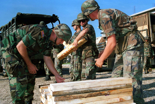 Lumber for desks and tables is unloaded from a truck and stacked at a school yard in Port-au-Prince by soldiers of the 27th Engineer Battalion, 20th Engineer Brigade, Ft. Bragg, NC. The desk legs were cut the day before to save time at the construction site. This is a civil affairs mission during Operation Restore Democracy