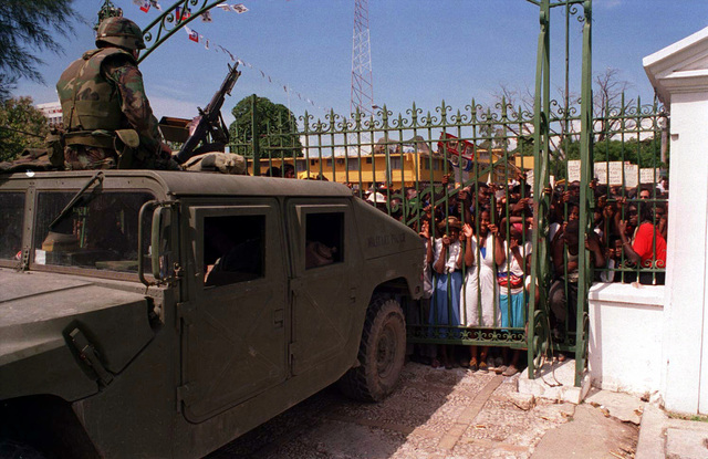 During Operation Uphold Democracy, an army soldier, wearing a flack vest, sits atop a High-Mobility Multipurpose Wheeled Vehicle (HMMWV) from the 55th MP Battalion mounted with an M60 machine gun. He is providing security just inside the gate of the Presidential Palace during the inauguration ceremony for President Jean-Bertrand Aristide who is being returned as president. Haitian supporters crowd the outside of the gate