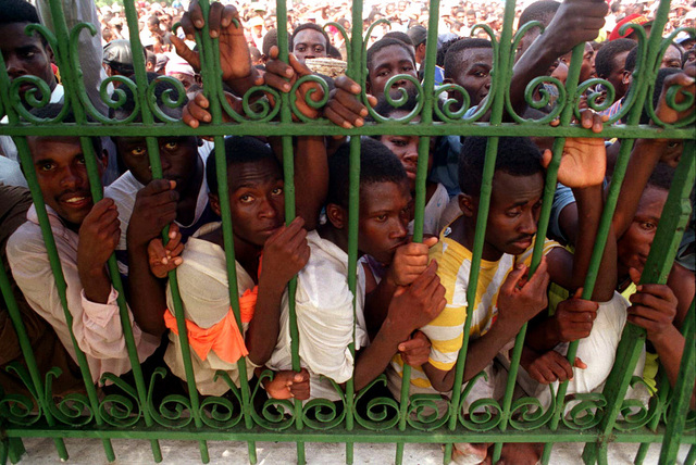 Haitians crowd the palace gate to show their support for President Jean-Bertrand Aristide during his inauguration at the National Palace at Port au Prince, Haiti during Operation Uphold Democracy. Thousands of people gathered outside the palace gate to cheer the return of their leader