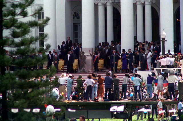 President Jean-Bertrand waves to the crowd of supporters and media from the steps of the Presidential Palace in Port au Prince on 15 Oct 1994. He was today returned to power during Operation Uphold Democracy