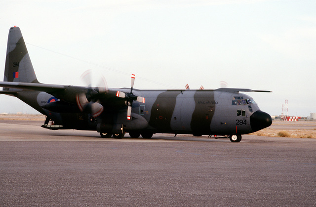 A right side view of a British C-130 from the Royal Air Force (RAF) lands at Kuwait International Airport. The aircraft is bringing passengers and equipment for their troops stationed in various parts of Kuwait. The British troops joined the United States forces in response to Saddam Hussein's advancement to the Kuwaiti border