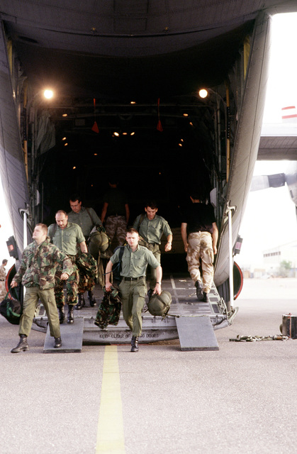 British troops depart a British C-130 after its arrival at Kuwait International Airport. The British troops joined the United States forces in response to Saddam Hussein's advancement to the Kuwaiti border