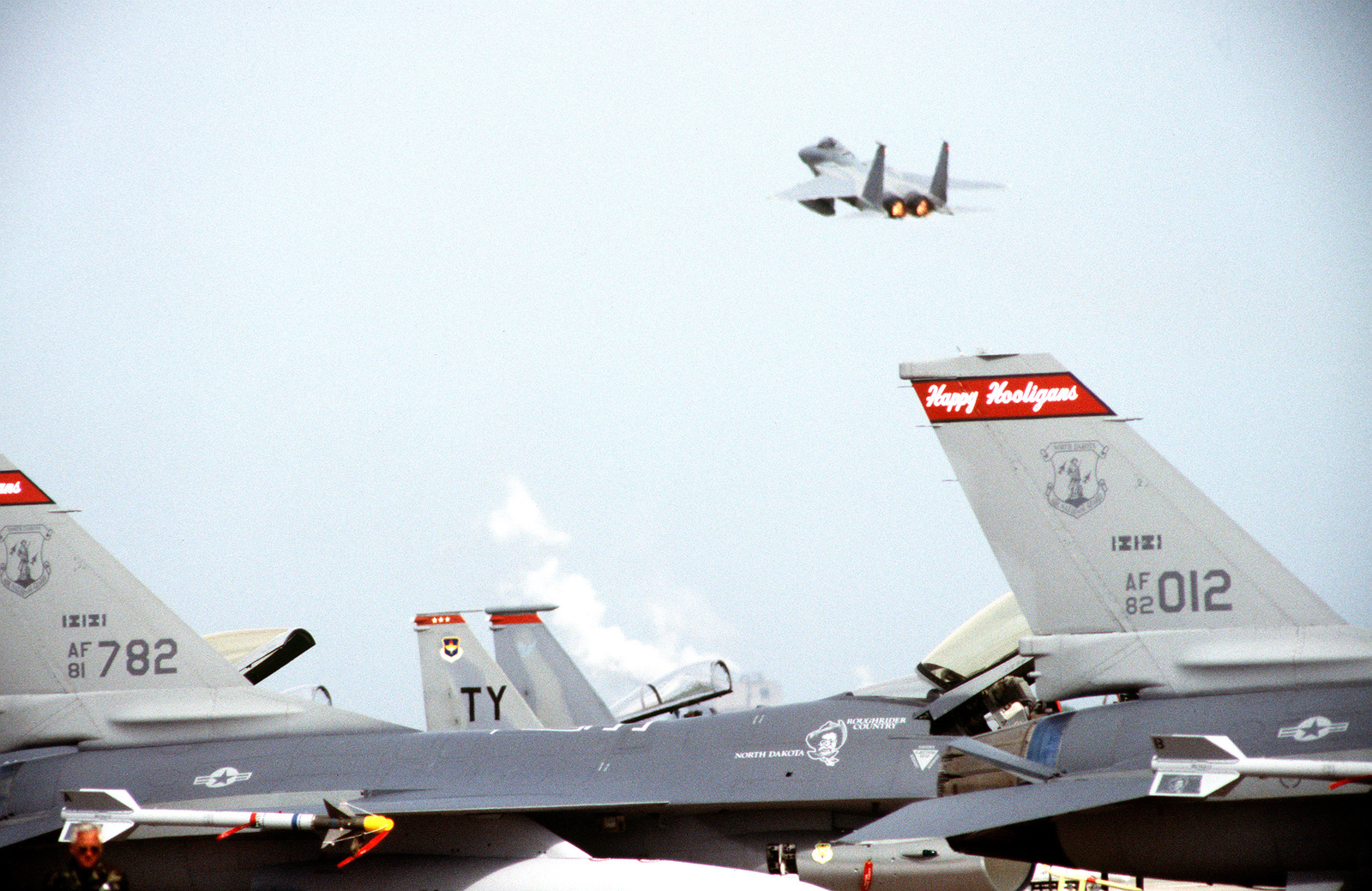 An F-15 Fighter aircraft from the 18th Fighter Wing, Kadena Air Base, Japan, takes off over F-16 Fighter aircraft sitting on the flightline during competition William Tell '94