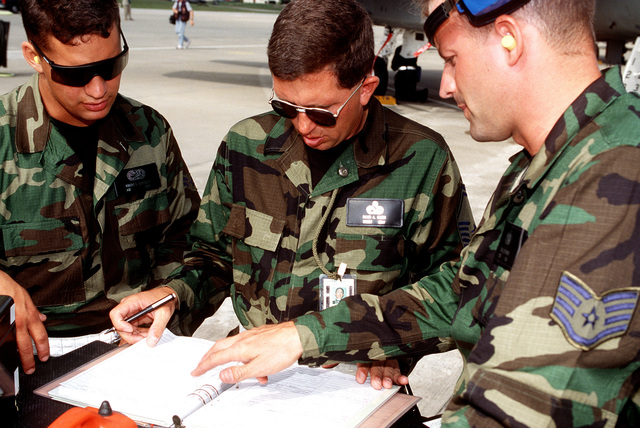 SENIOR MASTER SGT. David A. Glass (center), an officiating judge for competition William Tell '94, inspects the aircraft maintenance forms being worked on by AIRMAN 1ST Class Robert DePyssler (left) and STAFF SGT. Todd Sterner, both from the 33rd Fighter Wing, Eglin AFB, FL
