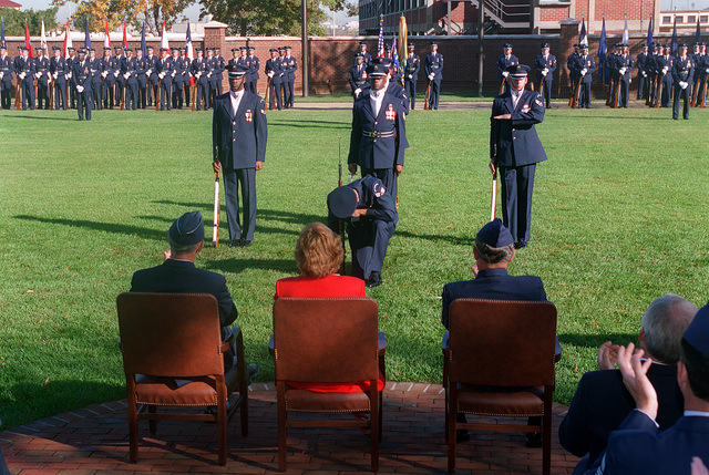 SENIOR AIRMAN Greg Quinn (left), TECH. SGT. John Warren (middle), and STAFF SGT. Flint Jernigan (right) of the United States Air Force Honor Guard perform of four man drill routine at CHIEF MASTER SGT. Gary Pfingston's retirement on the ceremonial lawn