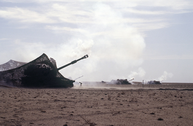 Smoke fills the air as US Army M109 A3 self-propelled Howitzers conduct live fire training at a training facility in the deserts of Kuwait. The Howitzers are covered with camouflaged netting