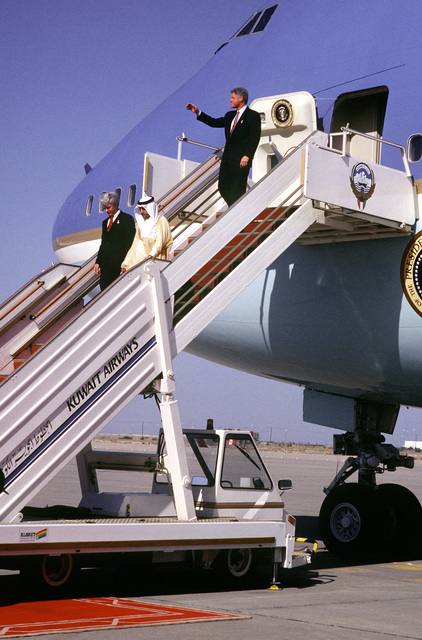 """President William Clinton waves as he descends the steps of Air Force One after his arrival at Kuwait International Airport. The President will visit troops at Liberty Base who are stationed with the 24th Mechanized from Fort Stewart and Fort Benning, and also receive the """"Mubarak Al-Kabeer"""" medal from Amir Sheikh Jabar Al-Ahmed Al-Sabah"""