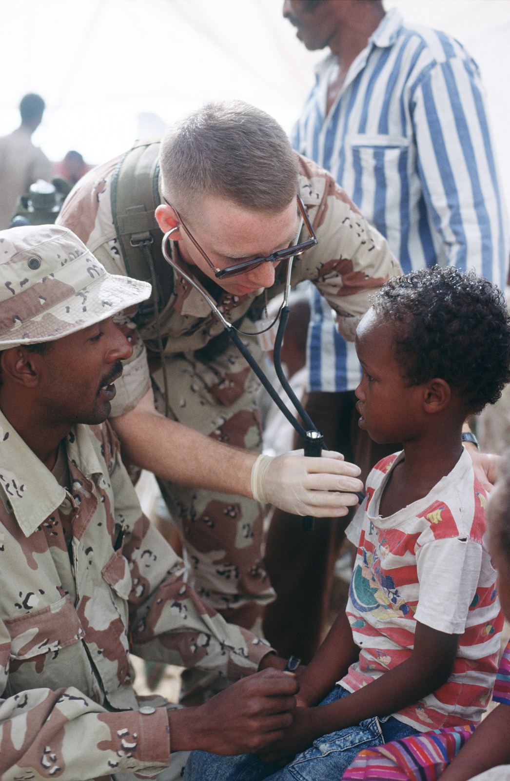 US Navy LT. Dennis Mckenna, a surgeon with the 46th Medical Task Force treat Somali children at a recent MEDCAP exercise. LT. Mckenna communicates with the children through the aid of an interpreter, Abdi Ahmed