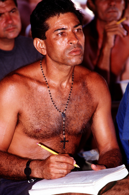 A Cuban migrant in Camp India takes notes during an English class given by Leo Tena, a fellow Cuban. Tena teaches the Cubans common phrases and customs they will need to know in the United States