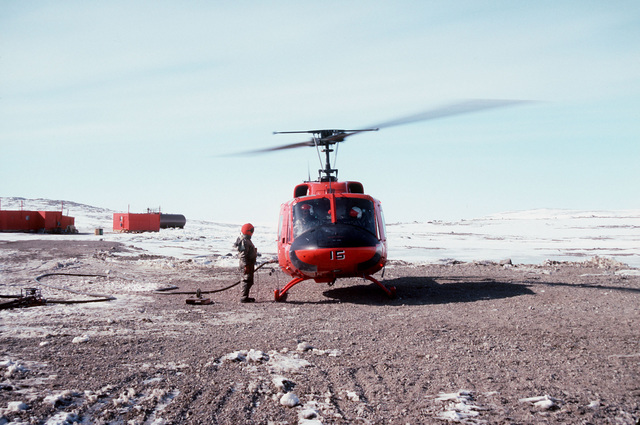 Front view of a UH-1 Iroquois Huey helicopter being fueled at McMurdo Sound prior to flying Vice Admiral Robert J. Spane, commander, Naval Air Force US Pacific Fleet out to one of the research sites