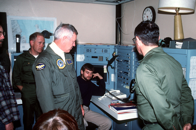 Vice Admiral Robert J. Spane, commander, Naval Air Force, US Pacific Fleet, is shown being briefed on the communications center operations at a site during an inspection tour