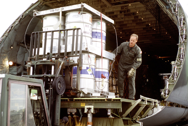 MASTER SGT. Walt Ramsey, 3rd Airlift Squadron, directs the loading of the canisters of radioactive materials onto a forklift