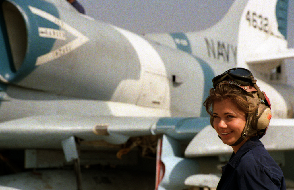 AIRMAN (AN) Mary Garcia, a plane captain for Fighter Squadron 126 (VF-126), stands next to the TA-4J Skyhawk