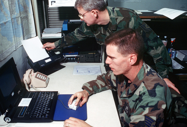 MSGT Donald G. Gunning (top) and SSGT Marc E. Allen (bottom) receive weather forecasts and satellite images via the Air Force Dial In System and check upper air flow charts. The weather forecasters are working out of a hangar on an Italian Air Force Base supplying weather data and forecasts to flight crews in support of operations over Bosnia-Herzegovina