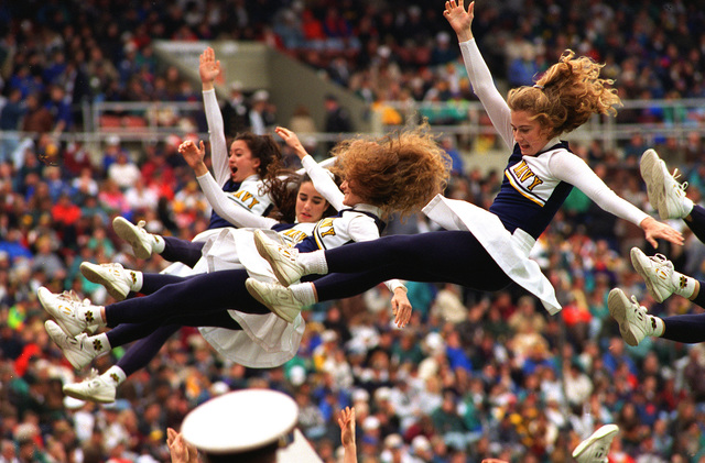 U.S. Naval Academy cheerleaders are tossed high in the air during the revelry associated with the annual Army-Navy football game at Veteran's Stadium