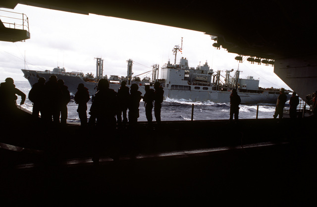 USNS PECOS (TAO 197) is framed by the opening of the hangar deck door of USS KITTY HAWK (CV-63) as the ships conduct an underway replenishment as part of the exercise