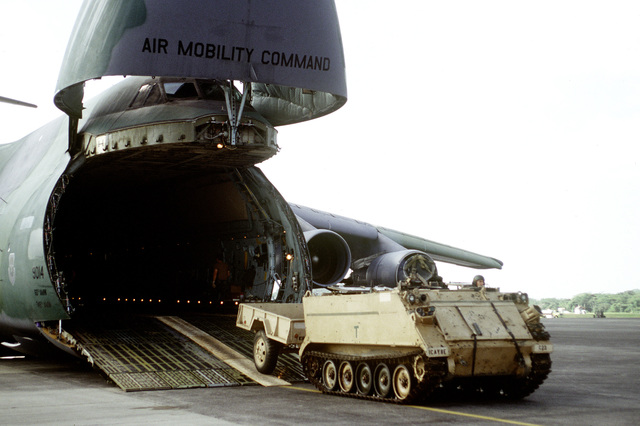 A U.S. Army M113A2 Armored Personnel Carrier is driven off a U.S. Air Force C-5 Galaxy at Howard AFB. The Air Force is flying in materials and personnel for increased activities during Operation Safe Haven