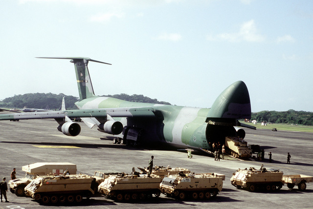 U.S. Army M113A2 Armored Personnel Carriers are off loaded from a U.S. Air Force C-5 Galaxy at Howard AFB. The Air Force is flying in materials and personnel for increased activities during Operation Safe Haven