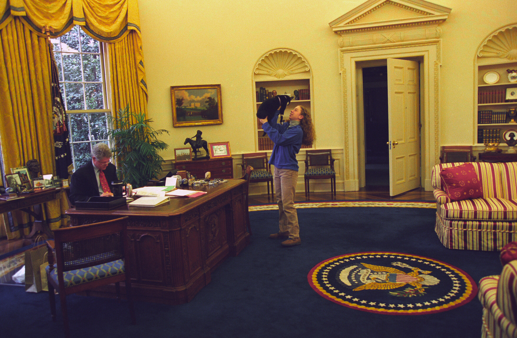 Photograph of Chelsea Clinton Playing with Socks the Cat in the Oval Office While President William Jefferson Clinton Works at his Desk
