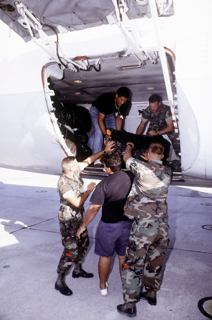 U.S. servicemen help Cuban repatriates pack their belongings onboard the airplane that will take them home. The migrants have volunteered to return home under the sponsorship of the International Organization for Migration (IOM)