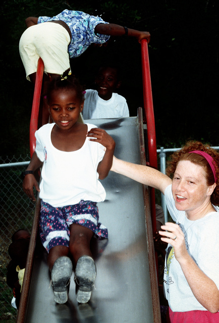 "CHIEF PETTY Officer Michele Hudak, Public Works Department, Iceland Defense Force, Keflavik, Iceland, helps a Haitian migrant down the slide at the elementary school at Naval Base Guantanamo Bay, Cuba. Hudak is a volunteer for the ""Love the Children"" program. This program offers base and Joint Task Force personnel an opportunity to spend time with the children"