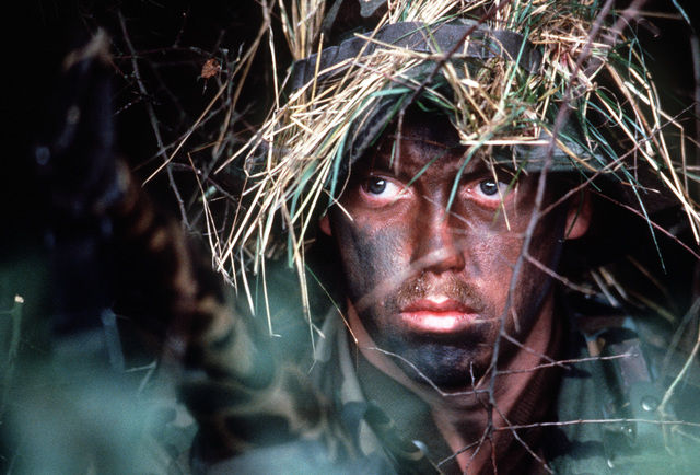 """A camouflaged member of an Air Force security police team defends a tactical airfield of the US Air Forces in Europe (USAFE) against """"enemy"""" forces during Exercise REFORGER, the annual return of forces to Europe of US and allied troops. AIRMAN-Magazine-Jan 1985"""